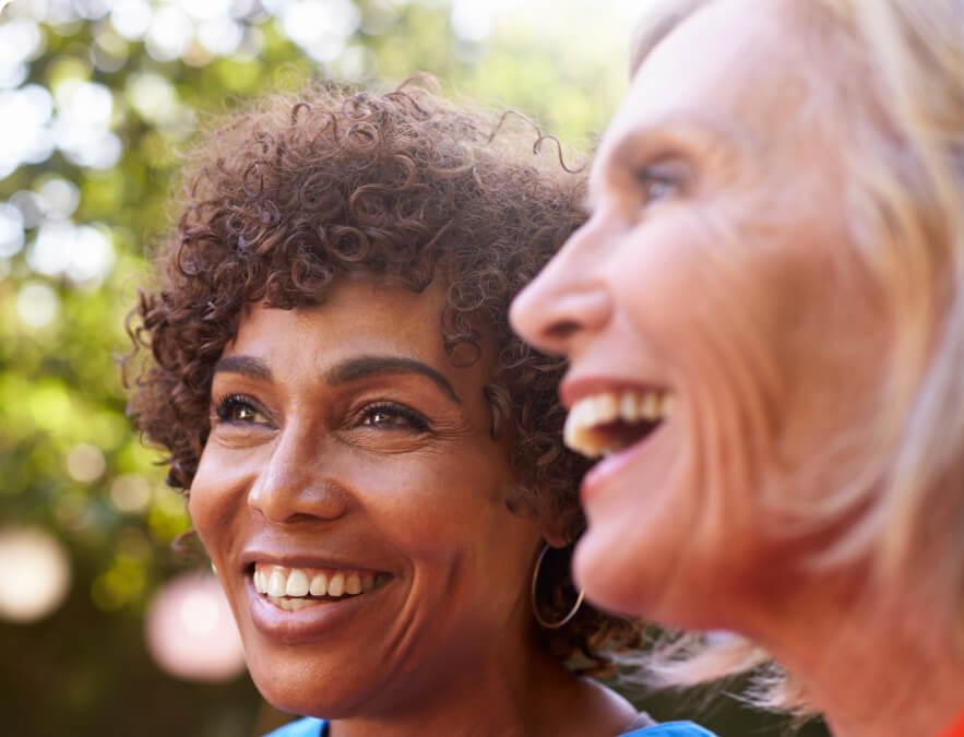 Two smiling elderly women outdoors