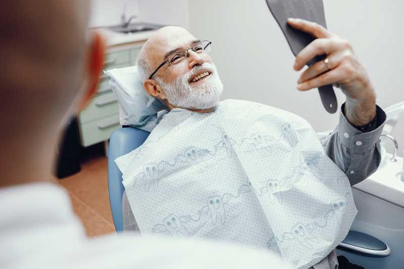 Elderly male patient admiring his smile in a handheld mirror
