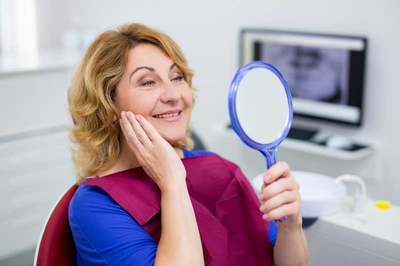 Middle-aged female patient admiring her smile in a handheld mirror